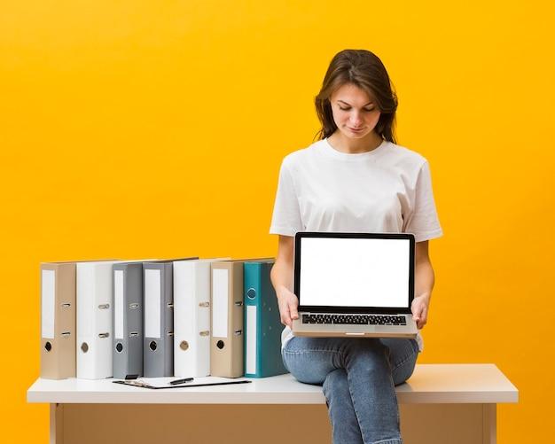 Vista frontal da mulher sentada na mesa e segurando laptop Foto gratuita