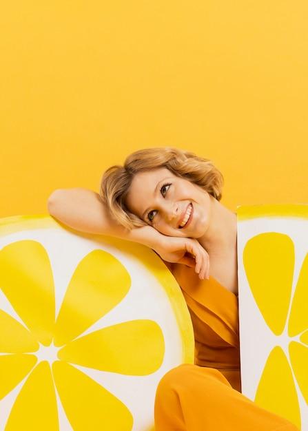 Vista frontal da mulher sorridente posando com fatias de limão decorações Foto gratuita