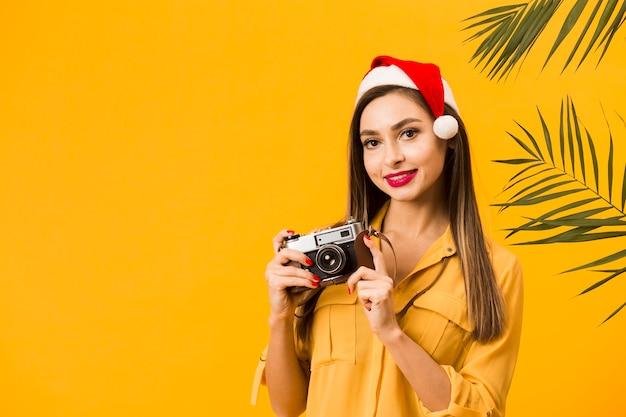 Vista frontal da mulher sorridente segurando a câmera enquanto usava chapéu de papai noel com espaço de cópia Foto gratuita