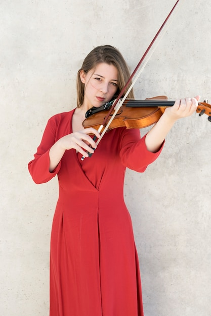 Vista frontal da mulher tocando violino Foto gratuita