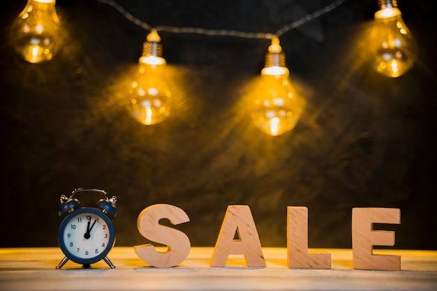 Vista frontal da palavra venda e lâmpadas com mesa de madeira Foto gratuita