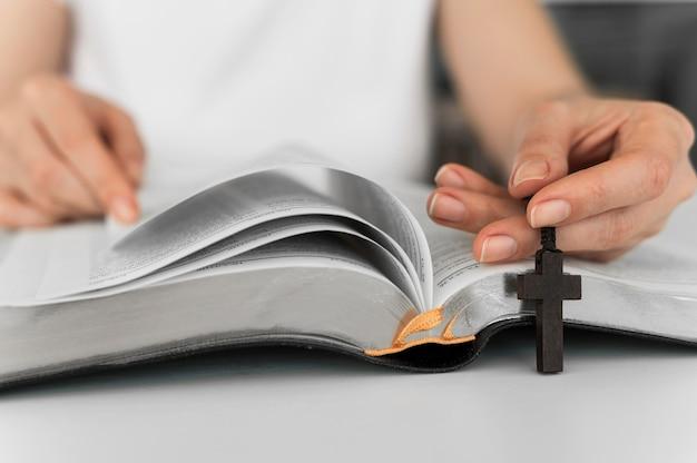 Vista frontal da pessoa com leitura cruzada do livro sagrado Foto gratuita