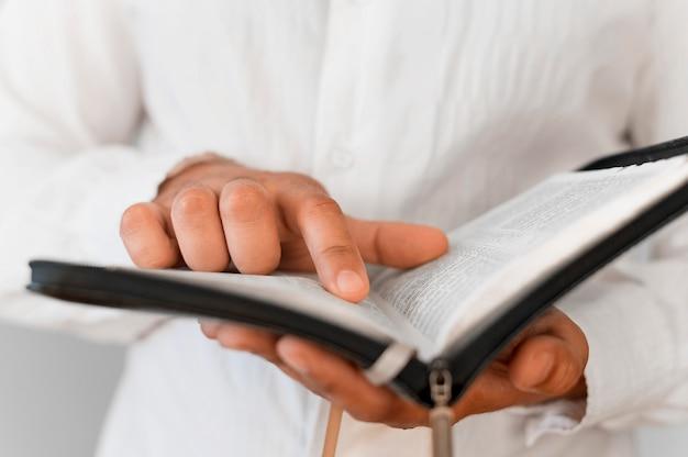 Vista frontal da pessoa lendo do livro sagrado Foto gratuita