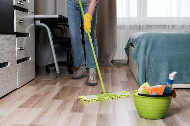 Vista frontal da pessoa limpando chão no quarto Foto gratuita