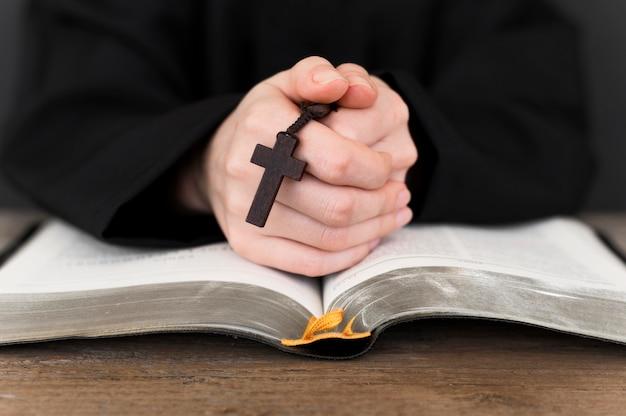 Vista frontal da pessoa orando com cruz e livro sagrado Foto gratuita