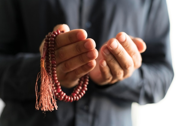 Vista frontal da pessoa orando com rosário Foto gratuita