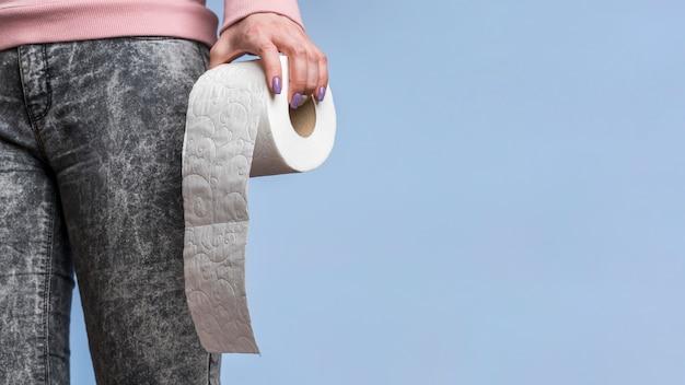 Vista frontal da pessoa segurando o rolo de papel higiênico com espaço de cópia Foto gratuita