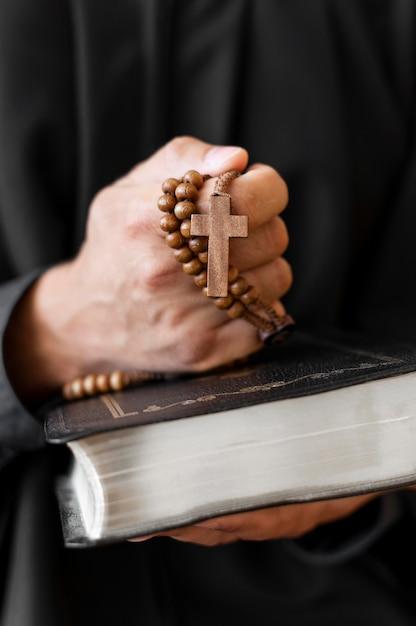 Vista frontal da pessoa segurando o rosário com cruz e livro sagrado Foto gratuita