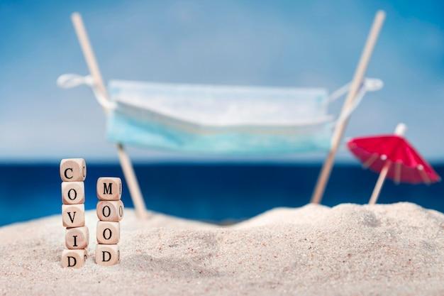 Vista frontal da praia com guarda-chuva e humor covid Foto gratuita
