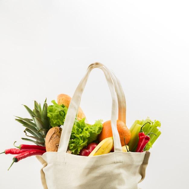 Vista frontal da sacola reutilizável com legumes e frutas Foto Premium
