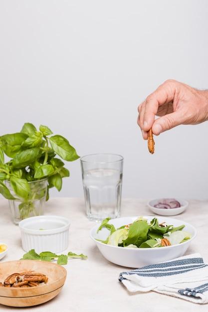 Vista frontal da salada em uma tigela com nozes Foto gratuita