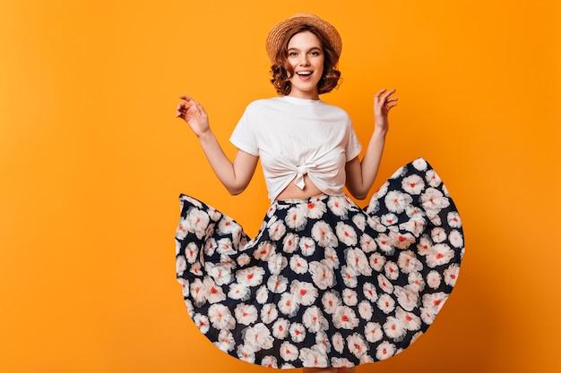 Vista frontal da senhora inspirada no chapéu de palha. foto de estúdio de linda garota sorridente com saia na moda, posando em fundo amarelo. Foto gratuita