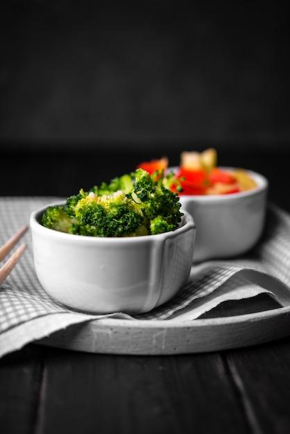 Vista frontal da xícara de brócolis no prato com pano Foto gratuita