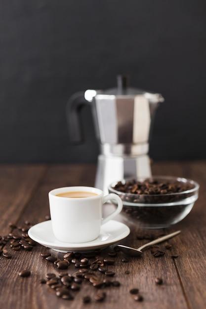 Vista frontal da xícara de café com panela e colher Foto gratuita