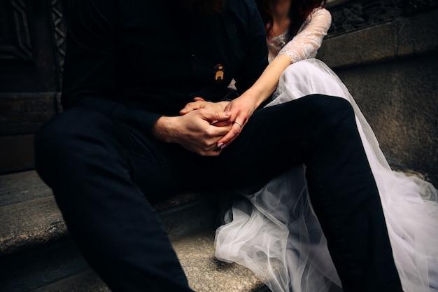 Vista frontal das mãos cruzadas do casal que está sentado na escada de pedra vestida em trajes de casamento Foto gratuita