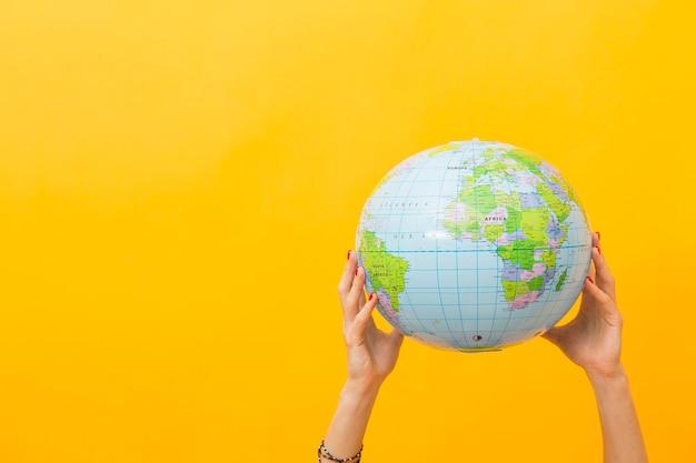 Vista frontal das mãos segurando um globo com espaço de cópia Foto gratuita