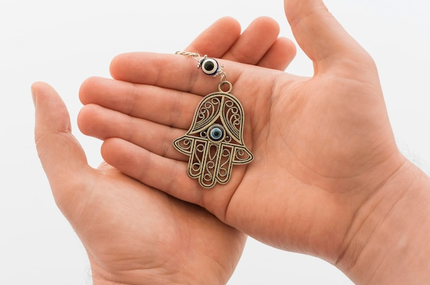 Vista frontal das mãos segurando um pingente de hamsa Foto gratuita