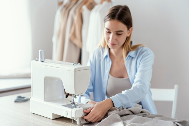 Vista frontal de alfaiate feminina usando máquina de costura no estúdio Foto Premium