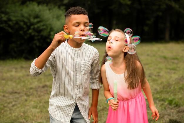 Vista frontal de amigos fazendo bolhas de sabão Foto gratuita