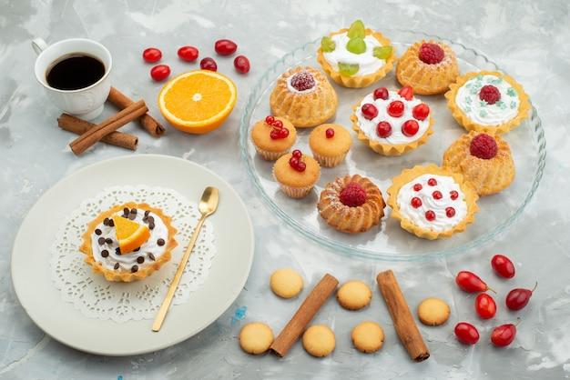 Vista frontal de bolos diferentes com biscoitos de canela e café na superfície clara açúcar doce fruta Foto gratuita