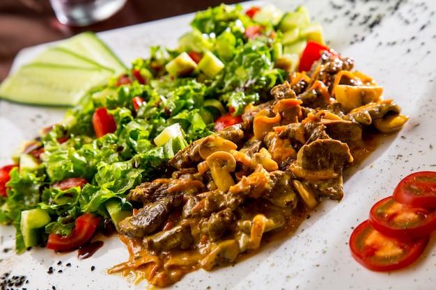 Vista frontal de carne frita com cogumelos em molho com salada de legumes e fatias de tomate e pepino Foto gratuita