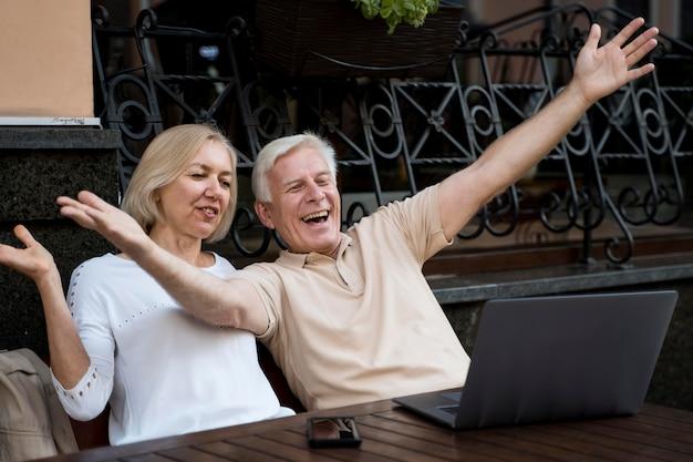 Vista frontal de casal sênior fazendo uma videochamada no laptop ao ar livre Foto gratuita
