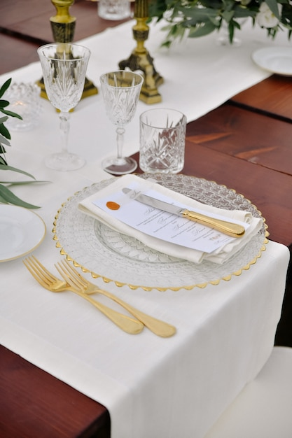 Vista frontal de copos e talheres servidos na mesa de madeira Foto gratuita