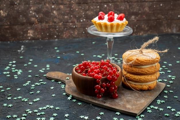 Vista frontal de cranberries vermelhos frescos dentro de uma tigela com recheio de creme e biscoitos de recheio na superfície escura bolo açúcar doce Foto gratuita