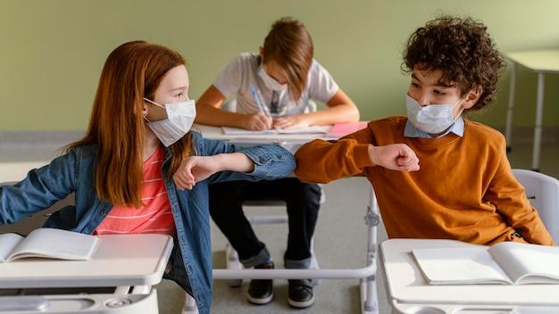 Vista frontal de crianças com máscaras médicas fazendo a saudação de cotovelo na aula Foto gratuita
