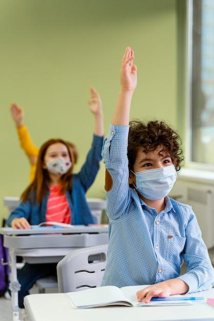 Vista frontal de crianças levantando as mãos na aula Foto gratuita