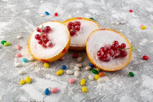 Vista frontal de deliciosos bolos de cranberry com cranberries vermelhas em pedaços de açúcar e pó Foto gratuita