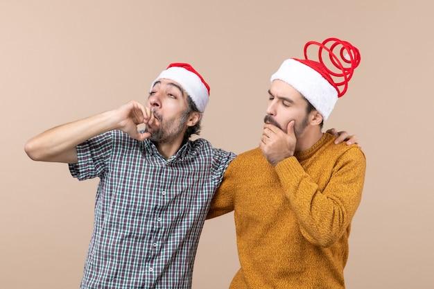 Vista frontal de dois caras atenciosos com chapéu de papai noel olhando para algo em um fundo bege isolado Foto gratuita