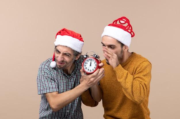 Vista frontal de dois homens perturbados querendo desligar o relógio em um fundo bege isolado Foto gratuita