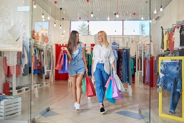 Vista frontal de felizes amigas saindo da loja de roupas Foto Premium