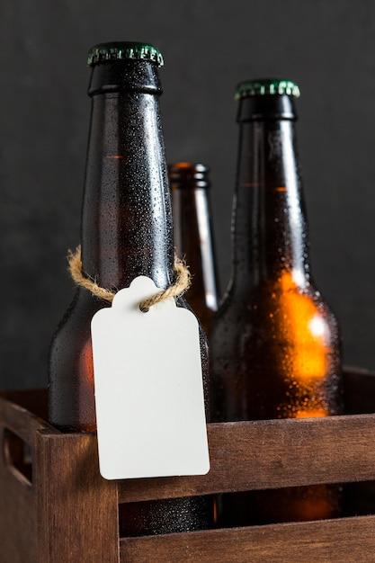 Vista frontal de garrafas de cerveja em uma caixa com etiqueta Foto gratuita