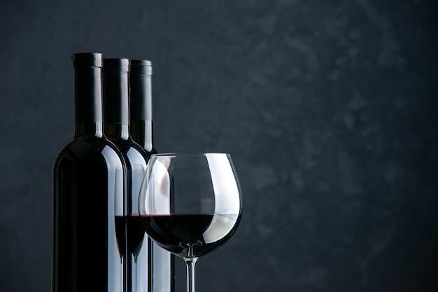 Vista frontal de garrafas de vinho com taça de vinho na superfície escura Foto gratuita