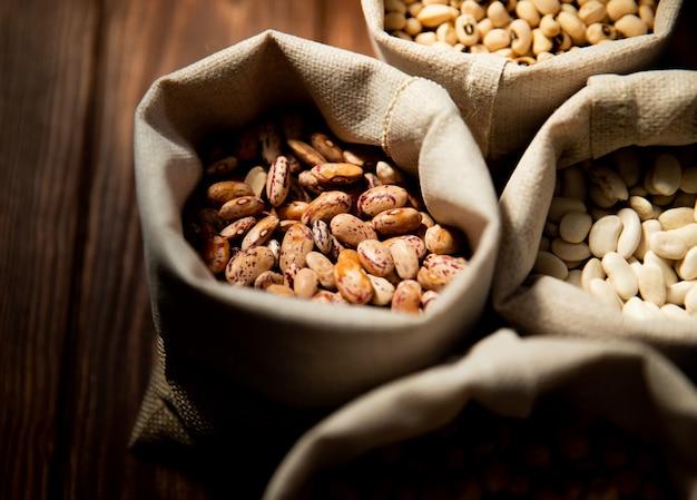 Vista frontal de grãos brancos e coloridos em sacos de estopa em uma superfície de madeira Foto gratuita