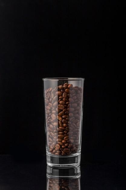 Vista frontal de grãos de café em copo alto Foto gratuita