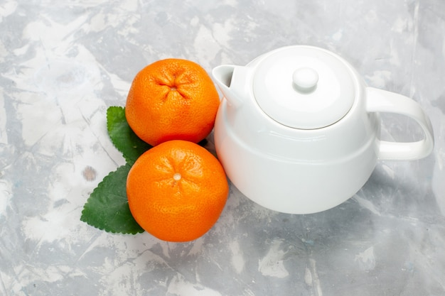 Vista frontal de laranjas frescas com chaleira na superfície branca Foto gratuita