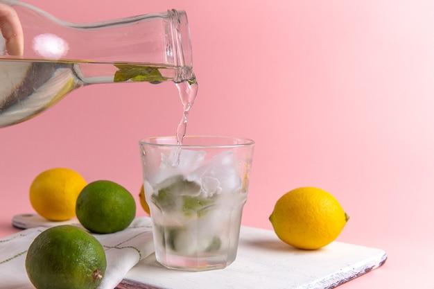 Vista frontal de limonada fresca com gelo dentro do copo e limões frescos na parede rosa Foto gratuita
