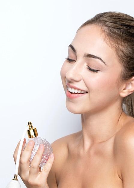 Vista frontal de mulher com frasco de perfume Foto gratuita