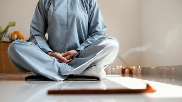 Vista frontal de mulher meditando Foto gratuita