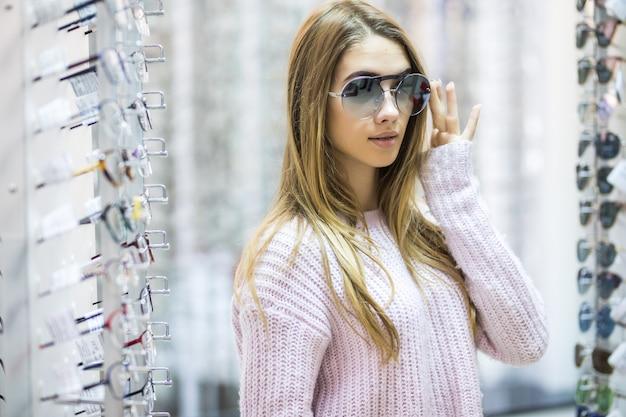 Vista frontal de mulher séria em suéter branco experimente óculos em loja profissional na Foto gratuita