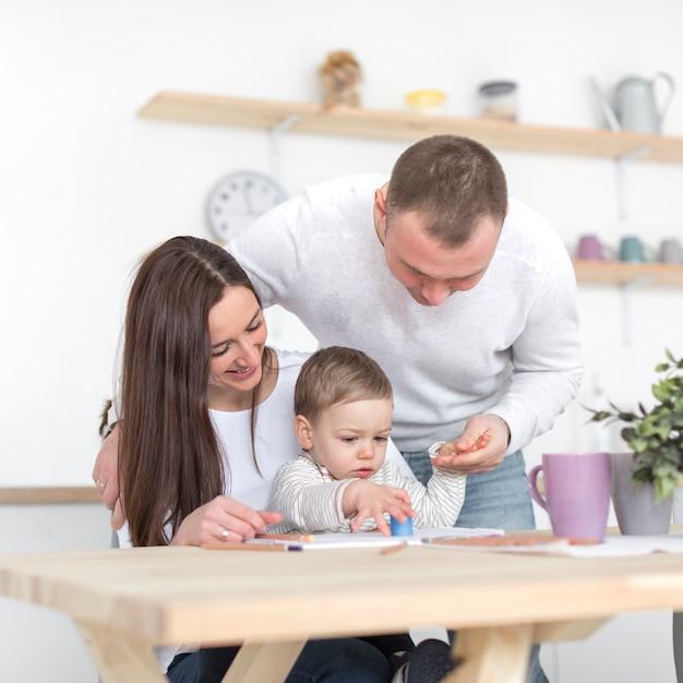 Vista frontal de pais felizes com bebê na cozinha Foto gratuita