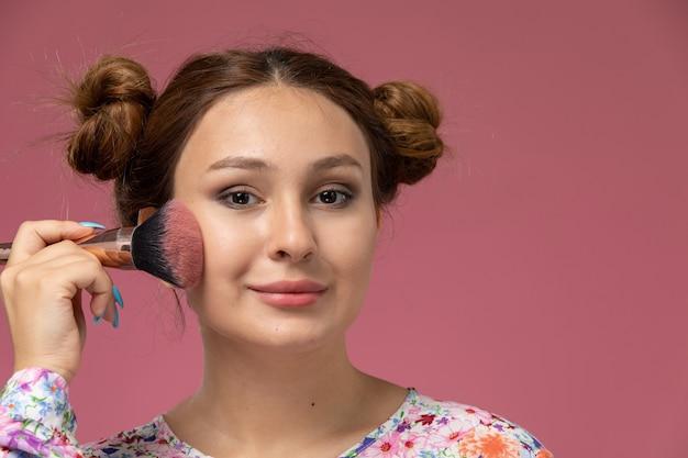 Vista frontal de perto jovem mulher com camisa com design de flor, fazendo maquiagem no fundo rosa Foto gratuita