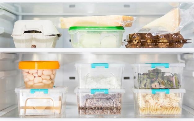 Vista frontal de recipientes de comida de plástico organizados na geladeira Foto gratuita