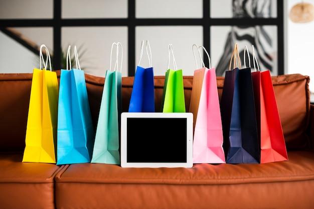 Vista frontal de sacos de papel coloridos e tablet Foto gratuita