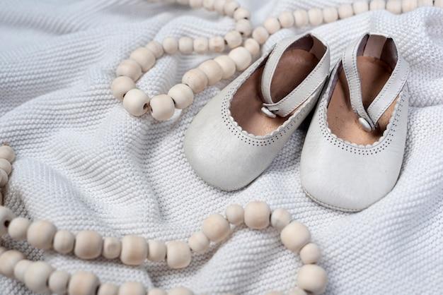 Vista frontal de sapatos de menina bonitinha no cobertor Foto gratuita