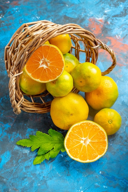 Vista frontal de tangerinas frescas na cesta de vime na superfície azul Foto gratuita