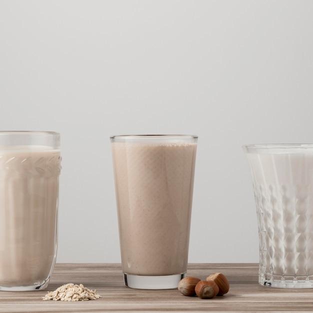 Vista frontal de três copos de leite diferentes Foto gratuita